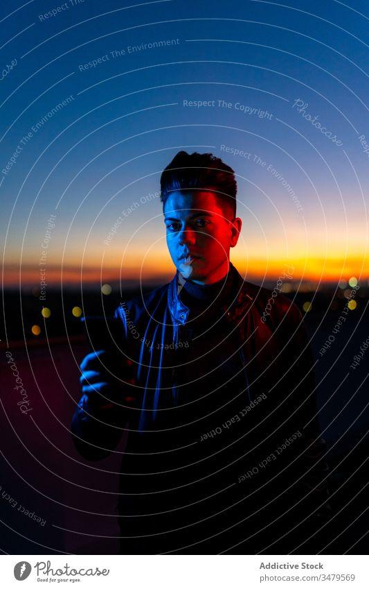 Hübscher Kerl am Telefon auf der nächtlichen Straße Mann neonfarbig Smartphone dunkel rot blau modern Nacht ernst Gerät leuchten Apparatur Mitteilung