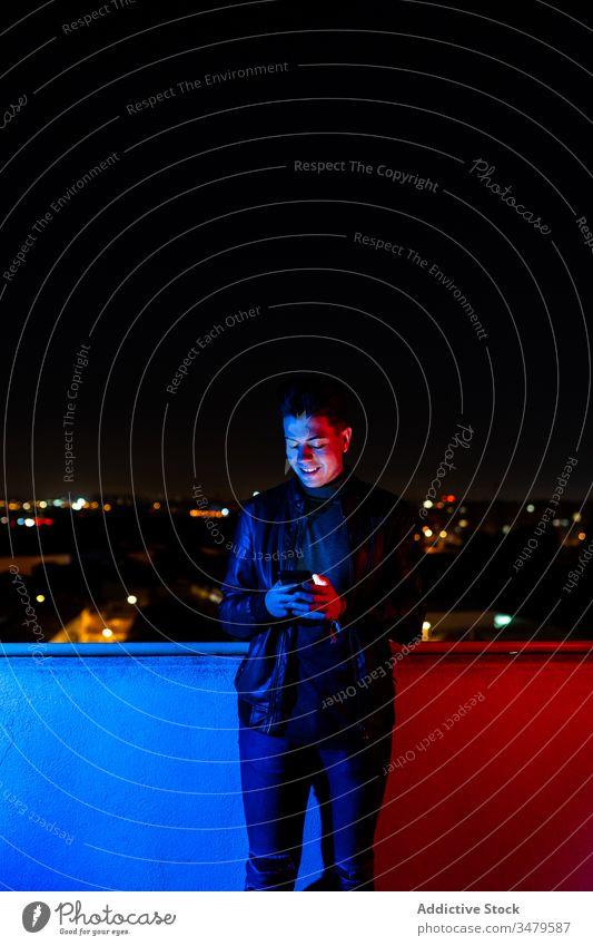 Junger Mann benutzt Smartphone auf beleuchtetem Balkon benutzend Nacht leuchten farbenfroh dunkel modern urban männlich Rotlicht blaues Licht Großstadt Gerät