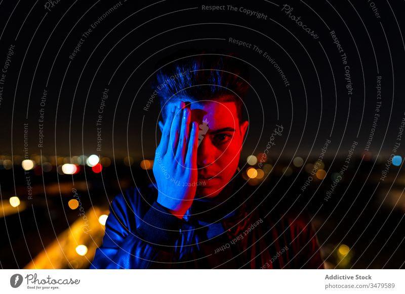 Moderner Mann bedeckt Gesicht unter farbiger Beleuchtung Deckblatt Hälfte Nacht leuchten Konzept Straße Großstadt urban dunkel männlich gestikulieren jung