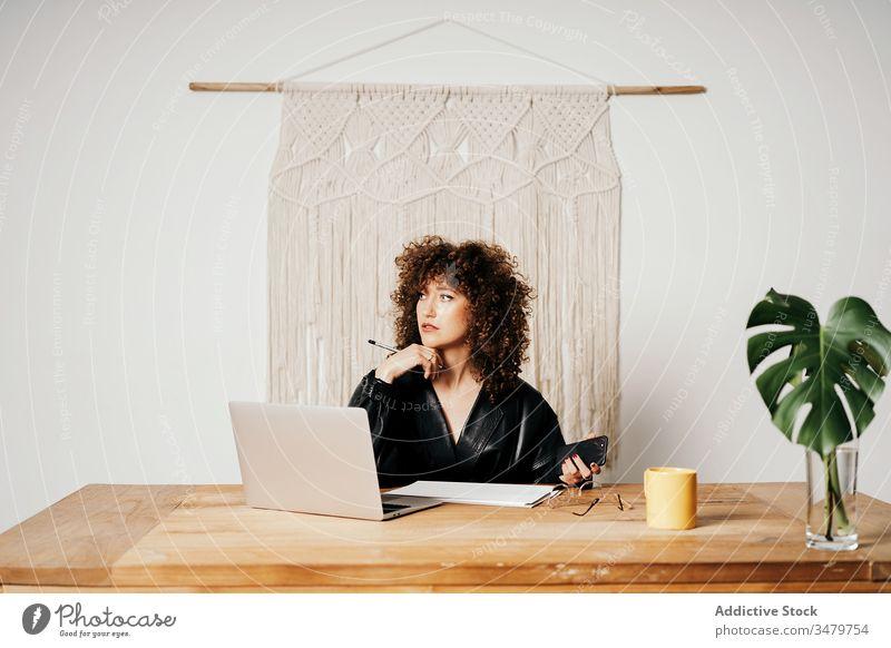 Im Büro arbeitende Retro-Geschäftsfrau Arbeit Laptop Daten lesen retro Tisch Leder sitzen Projekt Business Frau altehrwürdig krause Haare Job Apparatur Jacke