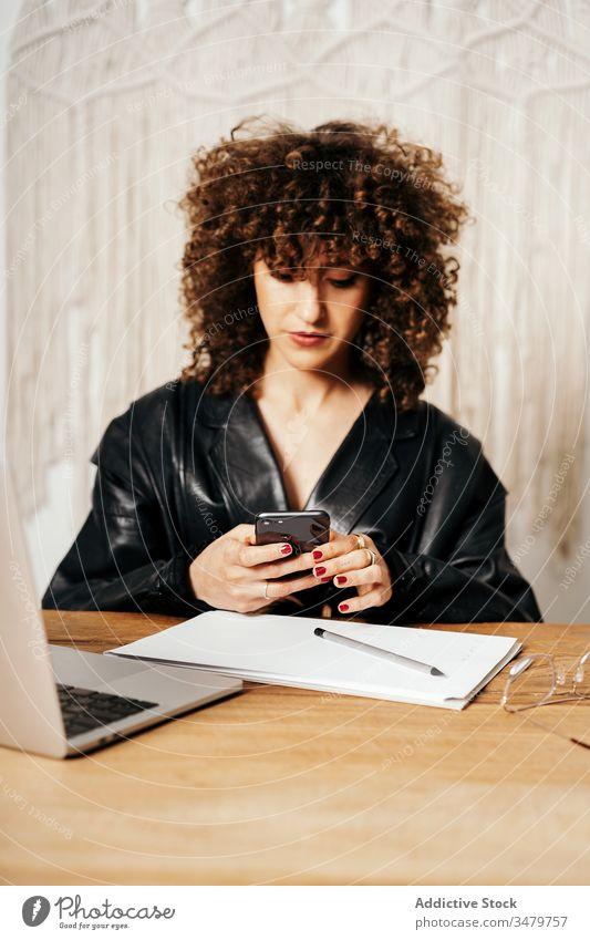 Vintage-Unternehmerin mit Smartphone, die sich Notizen macht Geschäftsfrau Notebook Büro benutzend retro Jacke Arbeit Frau Laptop Gerät Leder Apparatur
