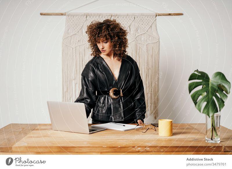 Vintage-Geschäftsfrau mit Laptop auf dem Tisch benutzend Büro Arbeit Leder Jacke sitzen retro Stil Outfit Frau Business cool Projekt Inbetriebnahme 80s Mode