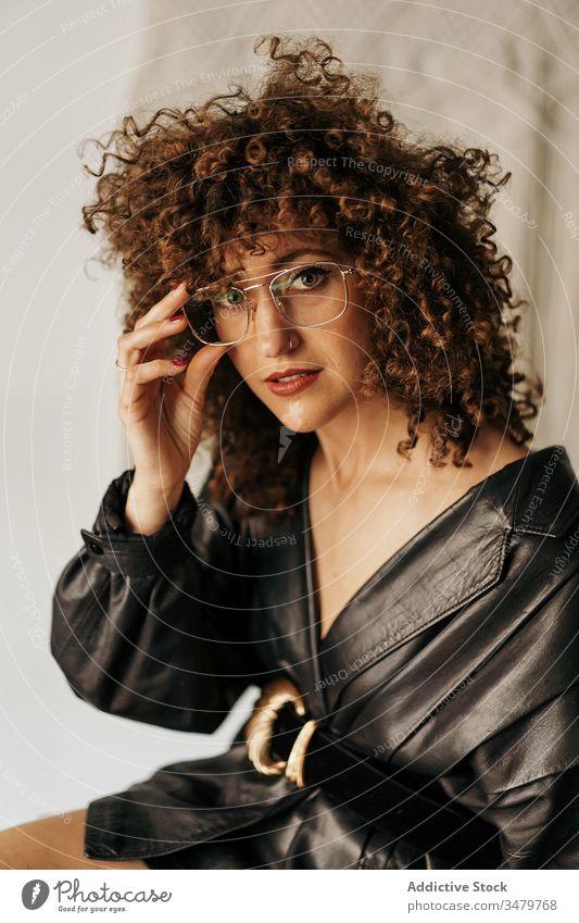 Retro-Unternehmerin beim Brillenanpassen Geschäftsfrau retro klug Leder Jacke Stil ausrichten Arbeit Erwachsener krause Haare Outfit Frau Business Kleid elegant