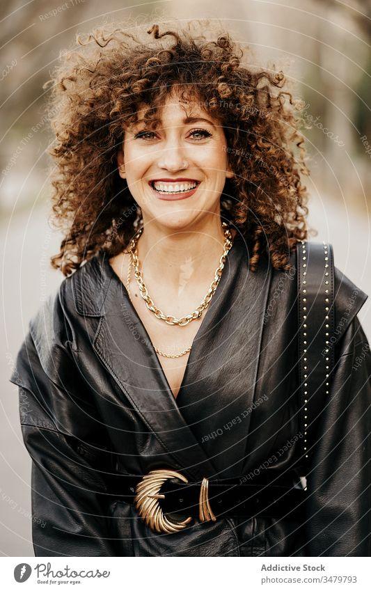 Begeisterte Retro-Geschäftsfrau auf der Straße retro Großstadt Lächeln Leder Jacke Erwachsener krause Haare Arbeitsweg Outfit Stil Glück Frau Freude Optimist