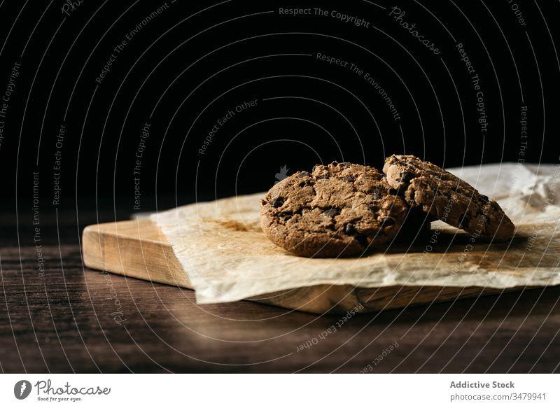 Leckere Schokoladenkekse auf Holztisch Keks hölzern gebacken Gebäck Biskuit süß Papier Lebensmittel Dessert dunkel geschmackvoll selbstgemacht Snack frisch