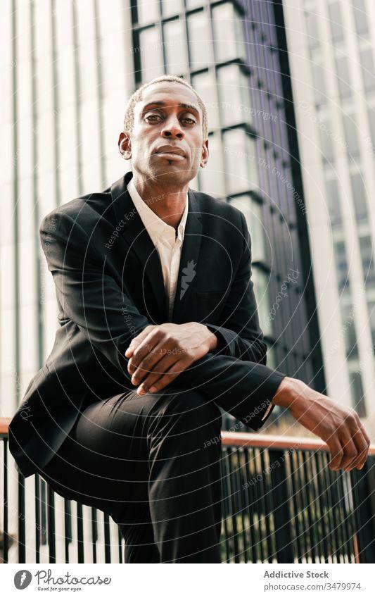 Selbstbewusster schwarzer Geschäftsmann lehnt sich an Geländer selbstbewusst modern Straße urban fettarm Reling ethnisch Großstadt Anzug männlich Hand-in-Tasche