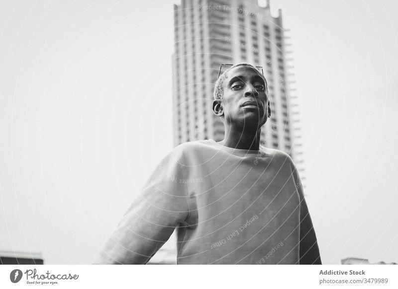 Trendiger afroamerikanischer Mann geht auf der Straße in der Stadt Stil Großstadt modern ethnisch unterirdisch Eingang selbstbewusst urban Outfit Lifestyle