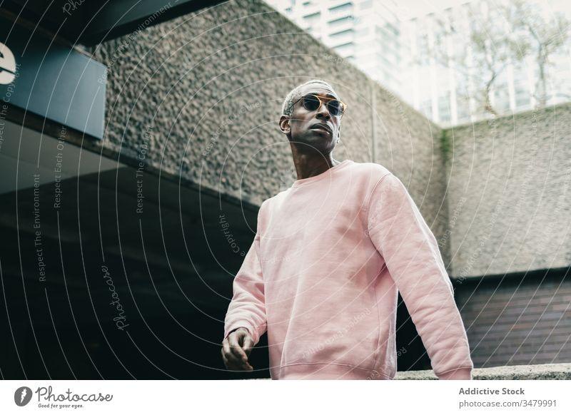 Trendiger afroamerikanischer Mann geht auf der Straße in der Stadt Stil Großstadt modern ethnisch unterirdisch Eingang selbstbewusst urban männlich Outfit