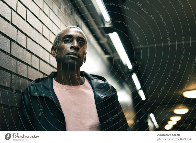 Afroamerikanischer Mann an Wand gelehnt Stil fettarm urban leuchten Gang ethnisch modern selbstbewusst männlich lässig trendy Mode cool Gebäude Großstadt
