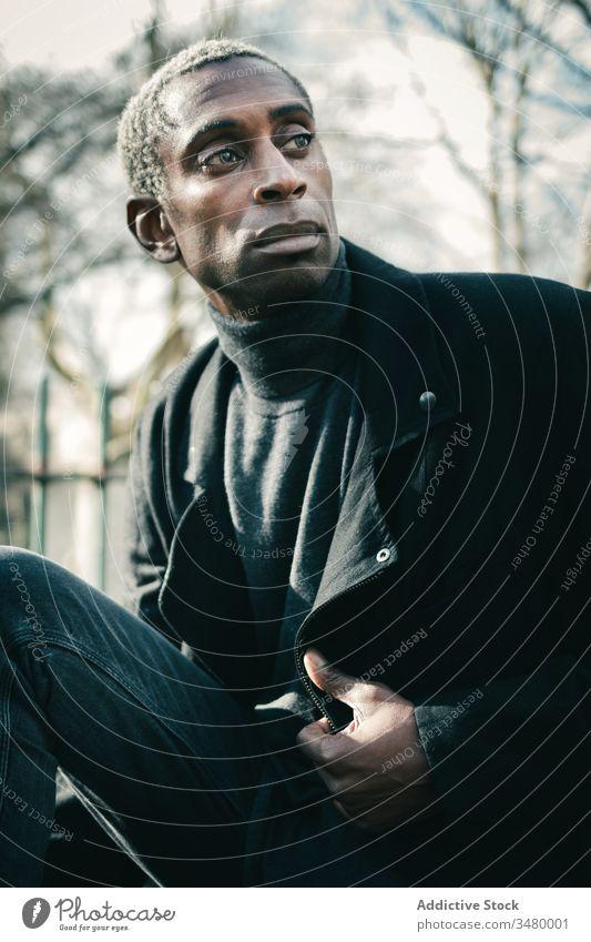 Trendiger afroamerikanischer Mann im Park Stil ruhen Großstadt ausrichten Jacke ethnisch urban modern männlich Lifestyle lässig trendy ernst selbstbewusst