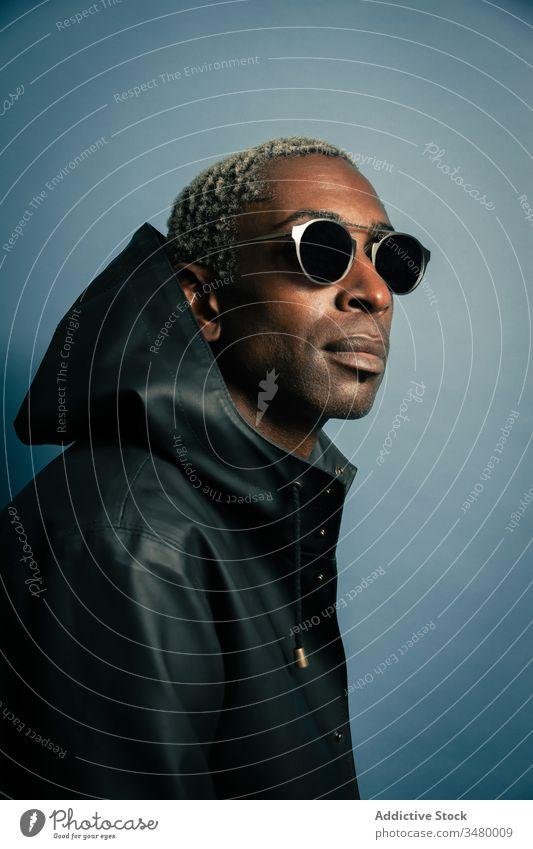 Erwachsener Mann mit Kapuzenmantel Stil modern Outfit ethnisch Mantel Sonnenbrille ernst selbstbewusst männlich trendy cool lässig Mode Zeitgenosse urban