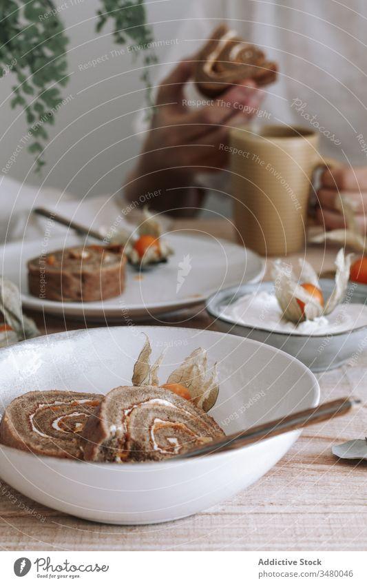 Gebackener Brötchenkuchen mit Physalisblüten rollen süß Kuchen Dessert Sahne selbstgemacht dienen Scheibe gebacken Lebensmittel lecker Teller geschmackvoll