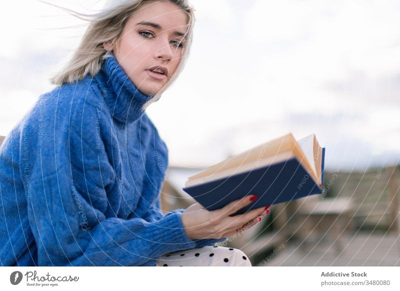 Junge Frau liest Buch an der Meeresküste Terrasse MEER Bank Strand ruhen lesen jung blau Pullover Natur sich[Akk] entspannen hölzern Stil Urlaub genießen