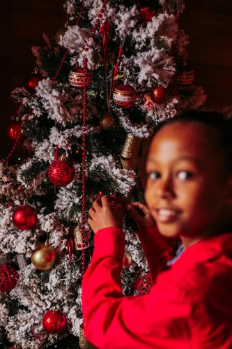 Glückliches kleines Mädchen schmückt den Weihnachtsbaum Kind Weihnachten Baum dekorieren Tradition heimwärts rustikal ethnisch Lächeln lässig heiter positiv