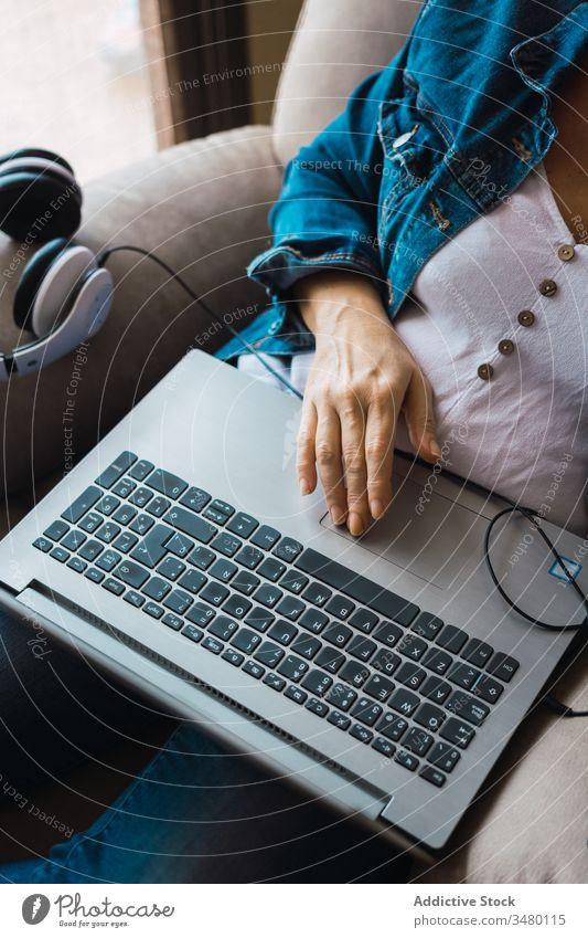 Freiberufler mit Laptop im Sessel Frau benutzend heimwärts freiberuflich Projekt Armsessel Kopfhörer sitzen Arbeit Erwachsener abgelegen Entfernung unabhängig