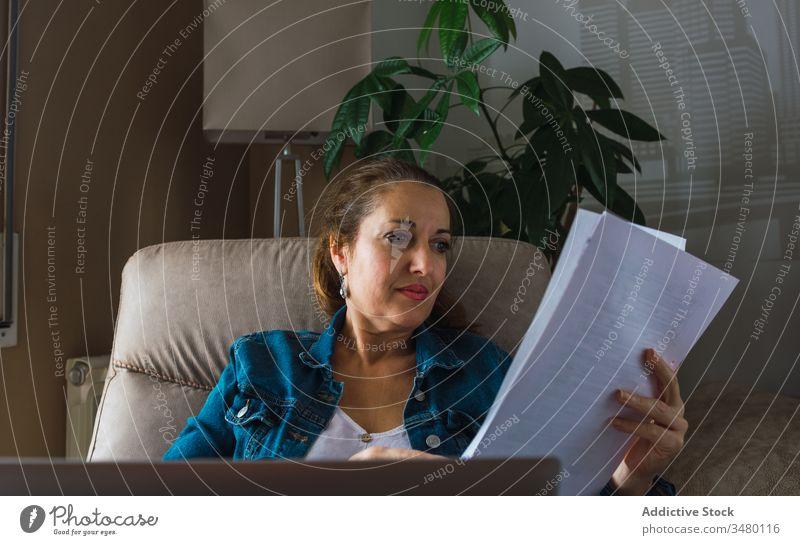 Erwachsener Freiberufler mit Laptop liest Dokument Frau freiberuflich lesen Papier benutzend heimwärts reif Fenster Armsessel sitzen Gerät Apparatur Drahtlos