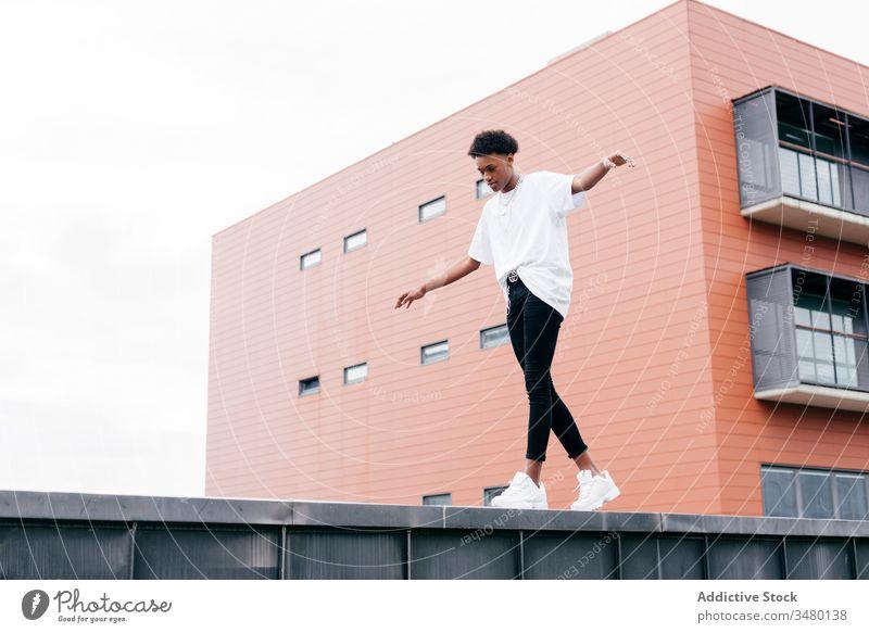 Modischer ethnischer Mann stellt sich gegen modernes Bauen Streetstyle Mode trendy cool urban Gebäude jung Großstadt selbstbewusst Afroamerikaner schwarz