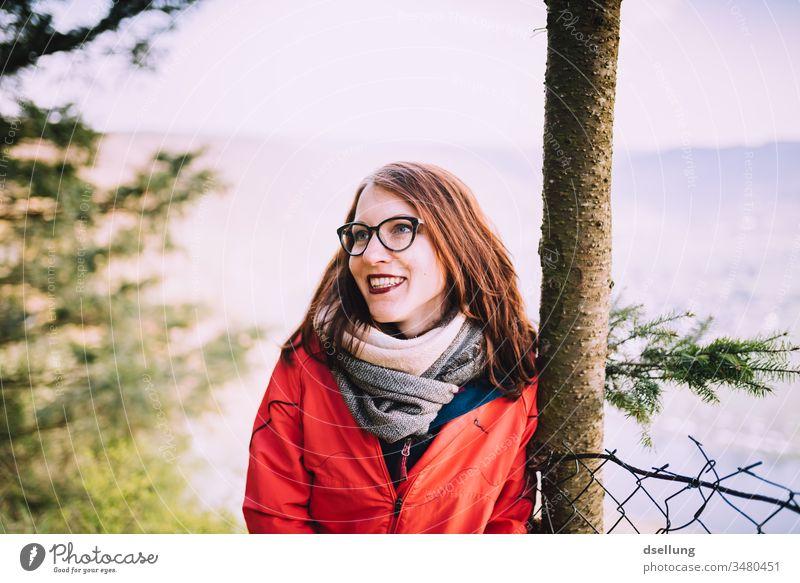 Junge Frau mit roter Jacke lehnt entspannt an einem Baum und lächelt mit der Sonne um die Wette spazierengehen Spaziergang Abenteuer Gesundheit Abstand Hügel