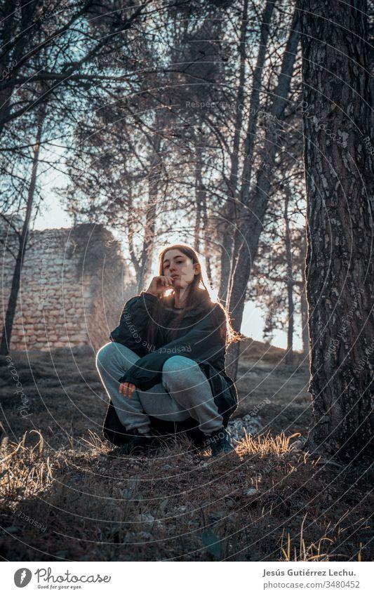 junges Mädchen mit ernstem Blick auf dem Gras sitzend mit starkem Kontrast im Hintergrund zur Sonne Vorderansicht Oberkörper Farbfoto Leben Spanien retro