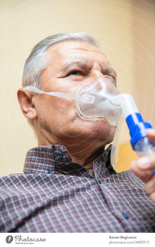 Älterer Mann mit medizinischer Ausrüstung zur Inhalation mit Atemmaske, Vernebler Aerosol Air Allergie Asthma Asthmatiker Atmung bronchiale Bronchitis Pflege