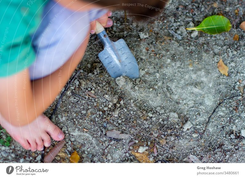 Barfüßiges Kind, das mit der Schaufel im Dreck wühlt Kinder Junge Sohn draußen spielen Schmutz Garten Gartenarbeit Außenaufnahme im Dreck spielen Menschen