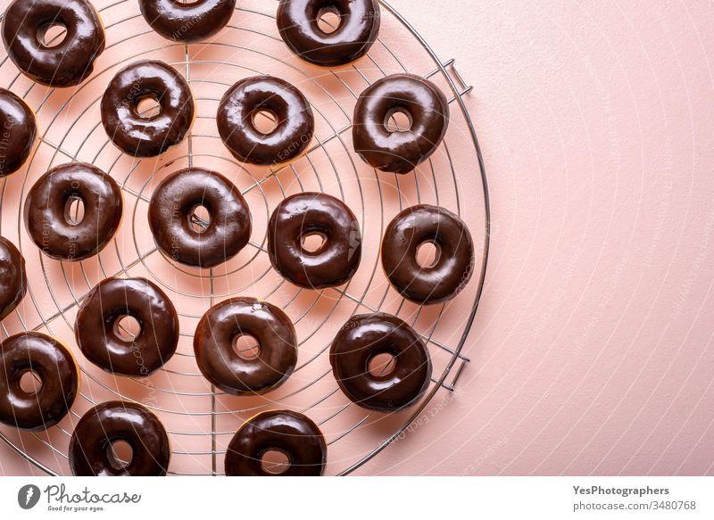 Heiße Donuts mit geschmolzener Schokolade auf einem Kühlgestell. Zubereitung von Schoko-Donuts obere Ansicht ausgerichtet Hintergrund Bäckerei Kohlenhydrate