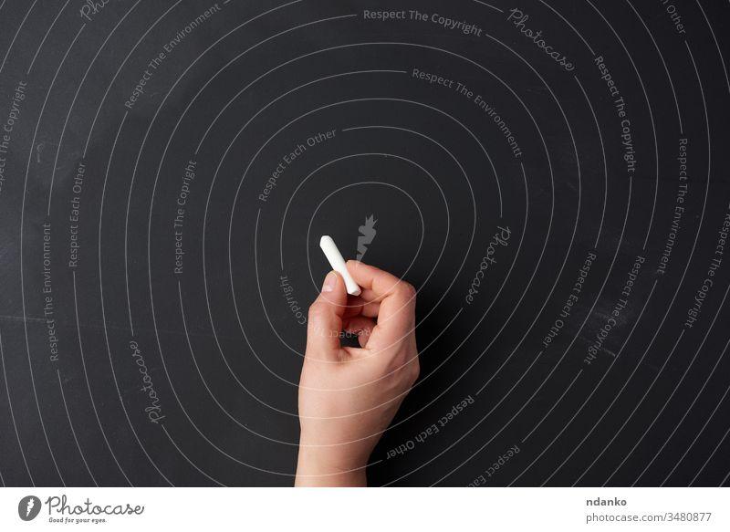 Hand hält ein Stück weiße Kreide auf dem Hintergrund einer leeren schwarzen Kreidetafel, Präsentationskonzept Halt blanko Zeichnung Schule lernen Klasse