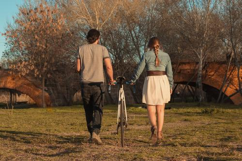 Verliebtes Paar Rücken an Rücken, auf dem Feld Mann Fahrrad Blumen Blumenstrauß Geschenk verliebt Freundin Valentinstag romantisch Romantik Erklärung Heirat