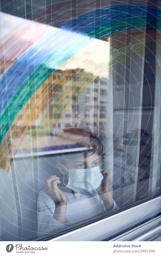Junge hinter Fenster während der Quarantäne Mundschutz medizinisch Regenbogen farbenfroh heimwärts Krankenhaus Stirnrunzeln Pandemie Coronavirus Bund 19 Kind