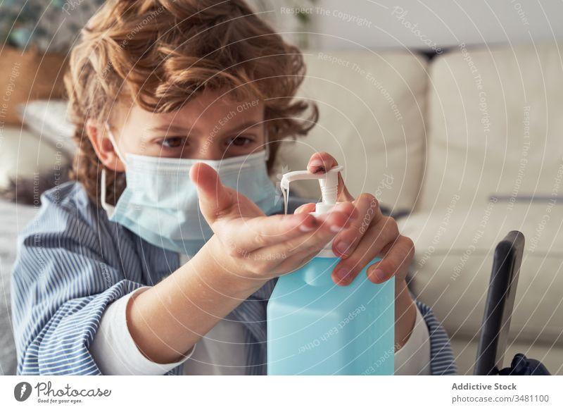 Junge mit medizinischer Maske desinfiziert Hände desinfizieren Hand Quarantäne heimwärts Mundschutz bewerben Flasche Spender Kind Desinfektionsmittel