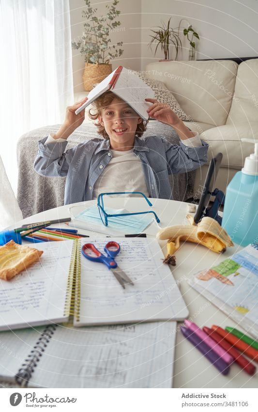 Gelangweilter Junge gähnt während Online-Studien abgelegen Bildung Quarantäne Lehrbuch gelangweilt gähnen Smartphone heimwärts Kind lernen Lifestyle Mundschutz