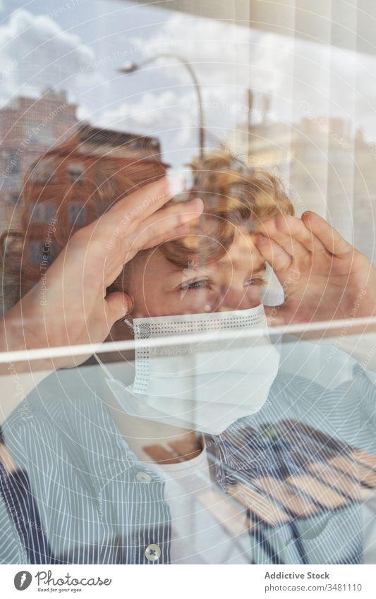 Junge hinter Fenster während der Quarantäne Mundschutz medizinisch heimwärts Stirnrunzeln Pandemie Coronavirus Bund 19 Kind Kindheit traurig unglücklich Hygiene