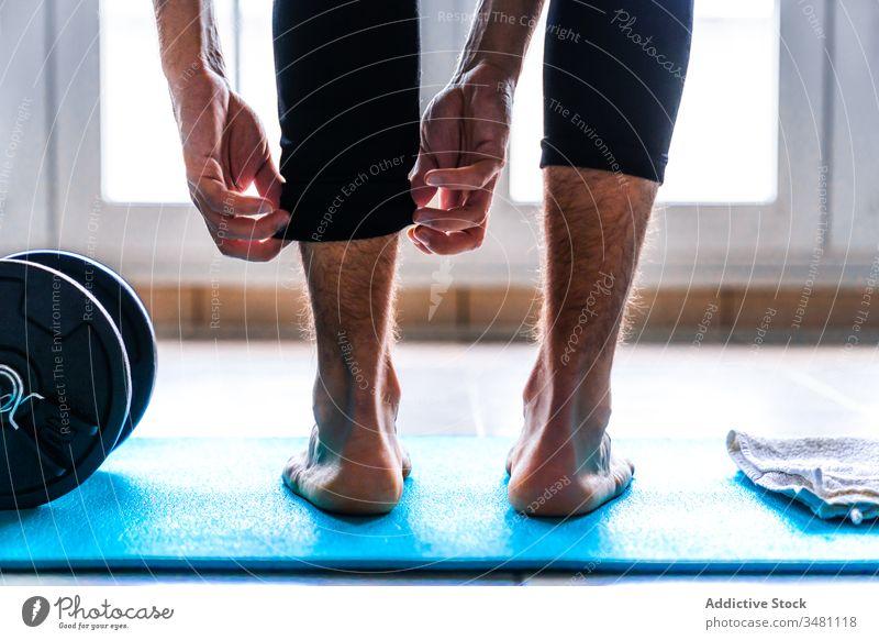 Fokussierter männlicher Athlet, der seinen Körper im Stehen auf einer Matte in einer leichten modernen Turnhalle dehnt Dehnung Fitnessstudio Bein Unterlage