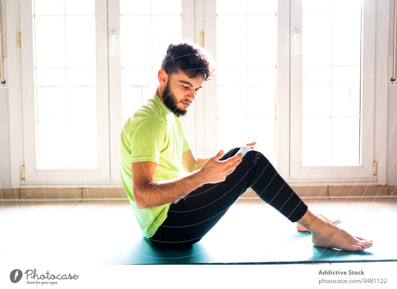 Nachdenklicher, entspannter Sportler, der ein Smartphone benutzt, während er sich nach dem Training auf einer Sportmatte im Leichtathletikraum ausruht Unterlage