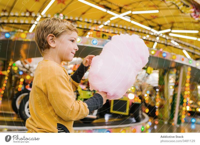 Junge isst Zuckerwatte auf Kirmes Jahrmarkt Lächeln Lichter Großstadt Fairness Entertainment Kind Glück urban süß Spaß erfreut Leckerbissen Lifestyle heiter