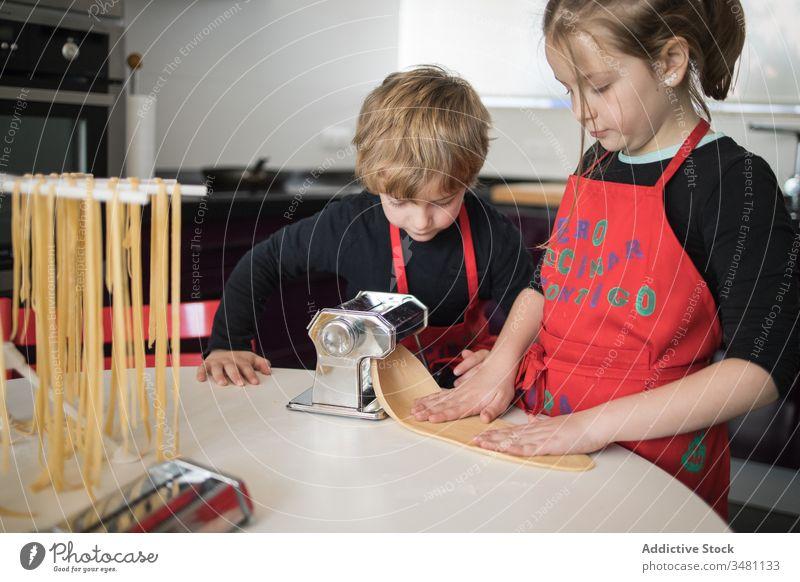 Kinder, die zu Hause Nudeln zubereiten Spätzle machen Maschine Zusammensein Geschwisterkind Küche selbstgemacht vorbereiten geschnitten Schwester Bruder