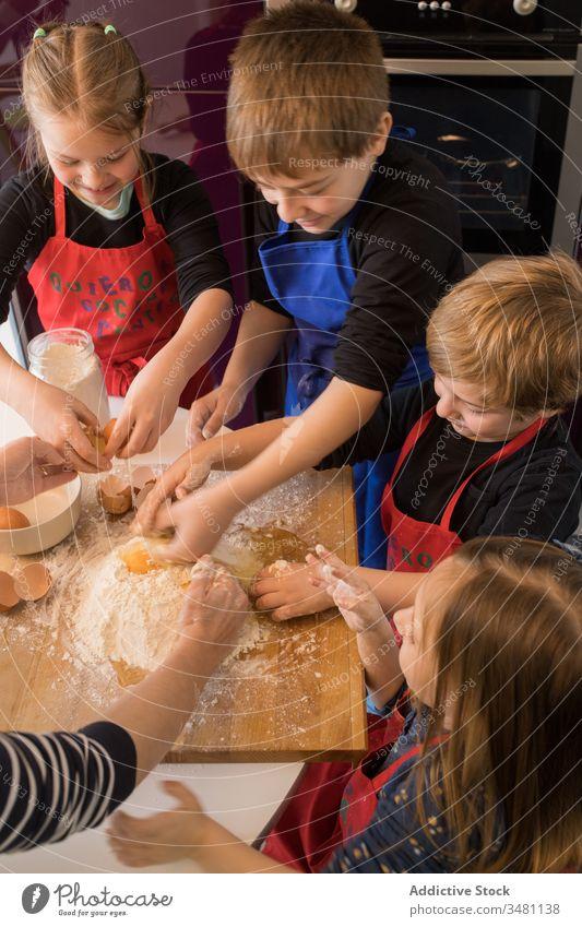Kinder bereiten gemeinsam Teig zu Küche Koch Teigwaren Mehl Zusammensein Tisch vorbereiten Lebensmittel Schürze niedlich Bestandteil Spätzle Hilfsbereitschaft
