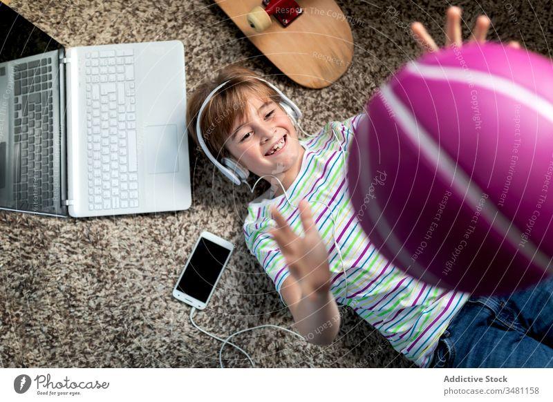 Glücklicher Junge hat Spaß zu Hause Kind Apparatur heimwärts Musik spielen Ball werfen räkeln Kopfhörer Smartphone sich[Akk] übergeben heiter zuhören Lügen