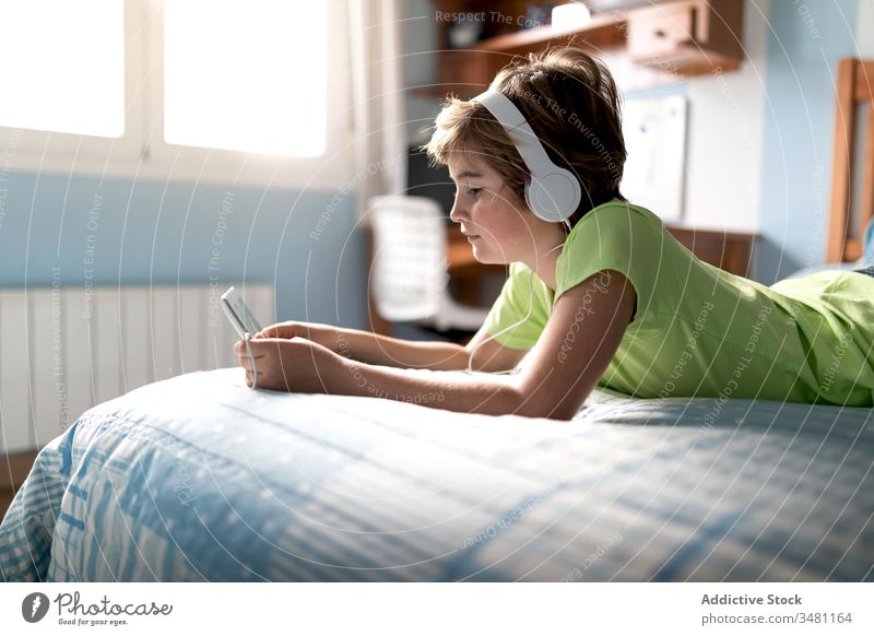 Fröhliches Kind sieht Film auf Tablett im Schlafzimmer Apparatur Tablette heimwärts zuschauen Kopfhörer heiter Junge benutzend Lachen online zuhören Internet
