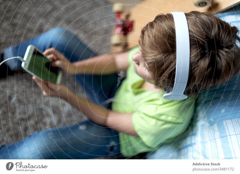 Kind mit Kopfhörern, das zu Hause ein Smartphone benutzt Apparatur heimwärts Junge benutzend Talkrunde Gerät online zuhören Internet Lifestyle modern Mobile