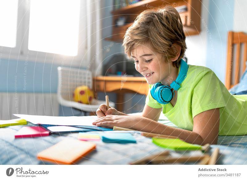 Kleiner Junge malt und hört Musik im Schlafzimmer Kind Kopfhörer zeichnen heiter heimwärts zuhören Kälte Glück farbenfroh Bleistift Drahtlos Lächeln Lifestyle