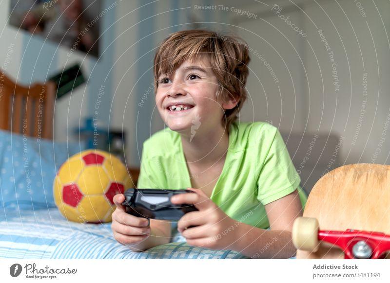 Glücklicher Junge spielt Videospiel im Schlafzimmer Kind Spaß spielen Gamepad Gerät aufgeregt Apparatur heimwärts Lügen heiter benutzend Konsole Bett Lifestyle