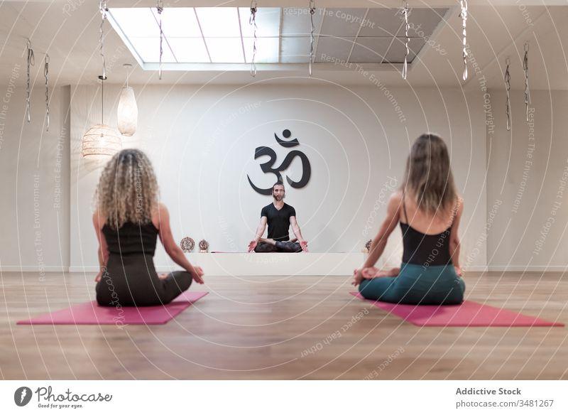 Gruppe von Menschen, die auf Lotus sitzen, posieren auf Matten Frauen Mann Lotus-Pose Yoga Raum Klasse Körper Gesundheit Mudra Erholung Training Zusammensein