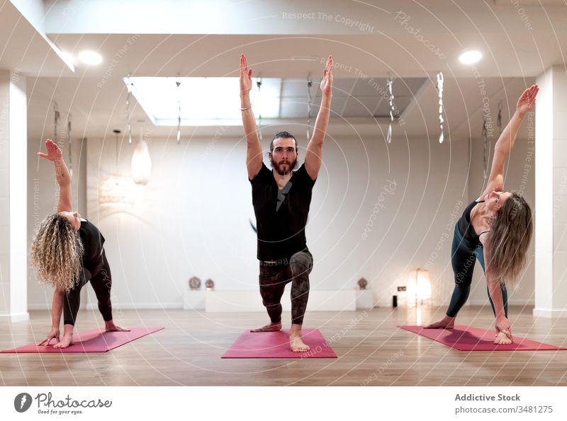 Gruppe von Menschen, die beim Yoga die Kriegerhaltung und die erweiterte Seitenwinkelhaltung einnehmen Frauen strecken Mann Raum Handreichung Krieger-Pose
