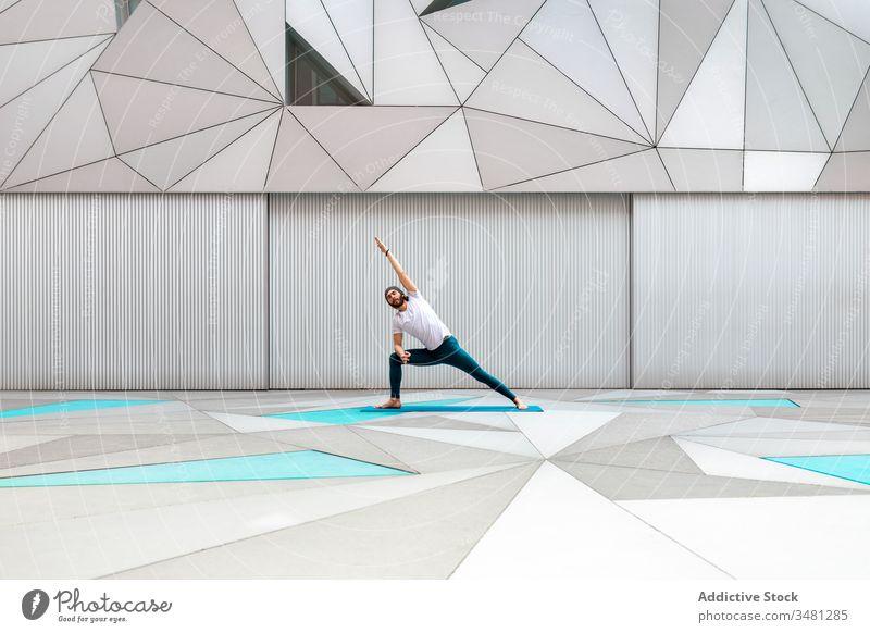 Mann macht Yoga-Übung im geometrischen Raum Training Geometrie Seitenwinkelstellung modern Dehnung Fitness Form männlich Sportbekleidung Architektur Zeitgenosse