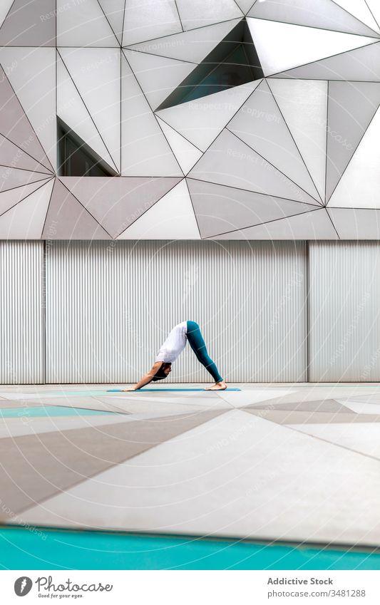 Mann macht Yoga in geräumigem Raum Übung Training Geometrie nach unten gerichtete Hundehaltung modern Dehnung Fitness Form männlich Sportbekleidung Architektur