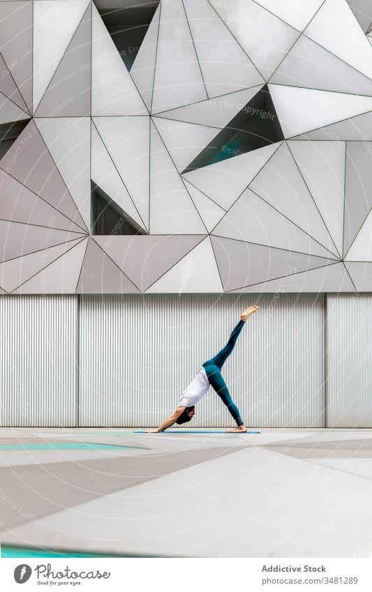 Schlanker Typ führt Yoga-Übung in geometrischem Raum aus Mann Training Geometrie modern Dehnung Fitness Form männlich Sportbekleidung Architektur Zeitgenosse