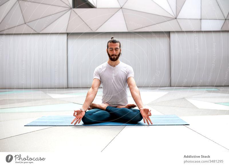 Bärtiger Mann meditiert während der Yogaausbildung meditieren Lotus-Pose Training Geometrie Augen geschlossen Gesundheit Übung sich[Akk] entspannen männlich