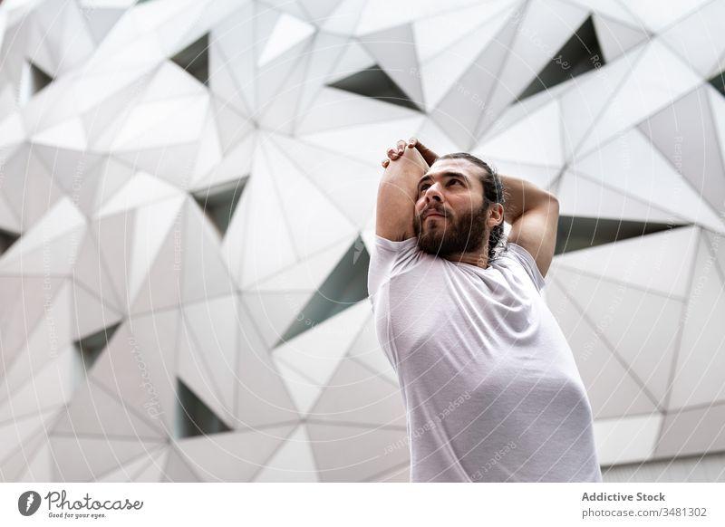 Bärtiger Mann streckt die Arme während des Yoga-Trainings Übung Geometrie Dehnung modern Fitness Form Wand männlich Sportbekleidung Architektur Zeitgenosse Zen