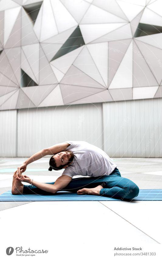 Flexibler Mann beugt sich beim Yoga-Training zum Bein Übung Geometrie gedrehte Kopf-zu-Knie-Haltung Wegbiegung modern Dehnung Fitness Form männlich